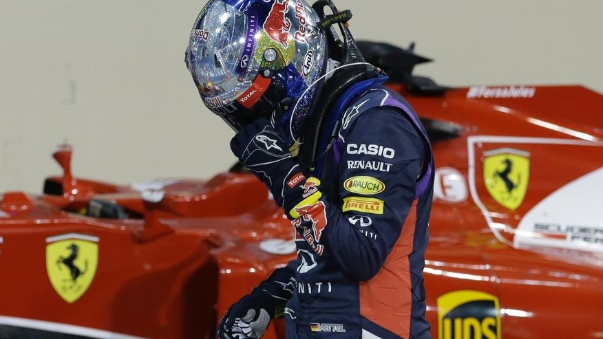 Red Bull driver Sebastian Vettel of Germany leaves his car after the qualifying session ahead of the Abu Dhabi Formula One Grand Prix at the Yas Marina racetrack in Abu Dhabi, United Arab Emirates, Saturday, Nov. 22, 2014. The Emirates Formula One Grand Prix will take place on Sunday. (AP Photo/Hassan Ammar)