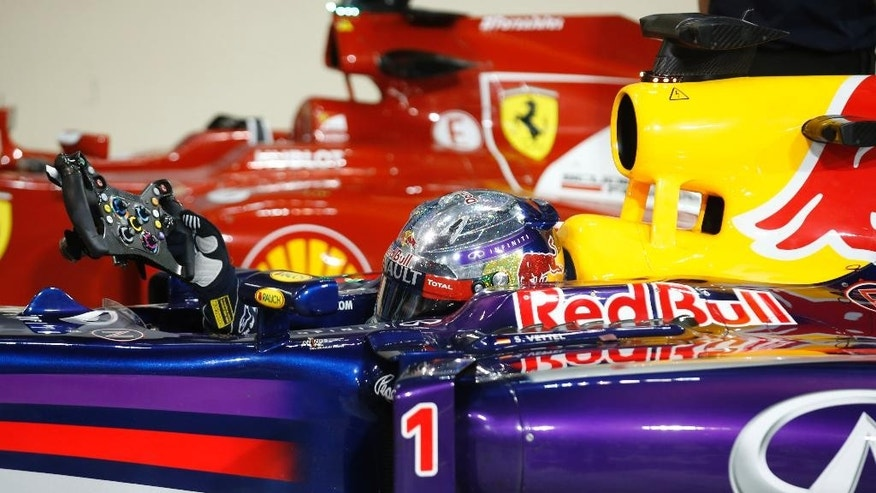 Red Bull driver Sebastian Vettel of Germany removes the steering wheel after the qualifying session at the Yas Marina racetrack in Abu Dhabi, United Arab Emirates, Saturday, Nov. 22, 2014. He clocked the sixth fastest time. The Emirates Formula One Grand Prix will take place on Sunday. (AP Photo/Luca Bruno)