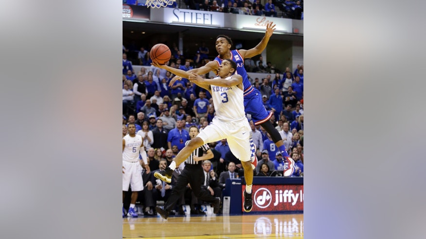 Kentucky's Tyler Ulis (3) puts up a shot against Kansas's Devonte Graham during the second half of an NCAA college basketball game Tuesday, Nov. 18, 2014, in Indianapolis. Kentucky won 72-40. (AP Photo/Darron Cummings)