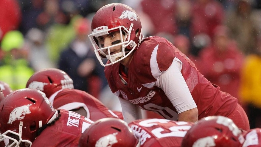 In this photo taken Nov. 22, 2014, in the first quarter of an NCAA college football game, Arkansas quarterback Brandon Allen, top, prepares for the snap against Mississippi. Arkansas gained bowl eligibility with its dominating win over Mississippi last week but the Razorbacks must get hobbled quarterback Allen healthy before Friday's game at Missouri. (AP Photo/Danny Johnston)