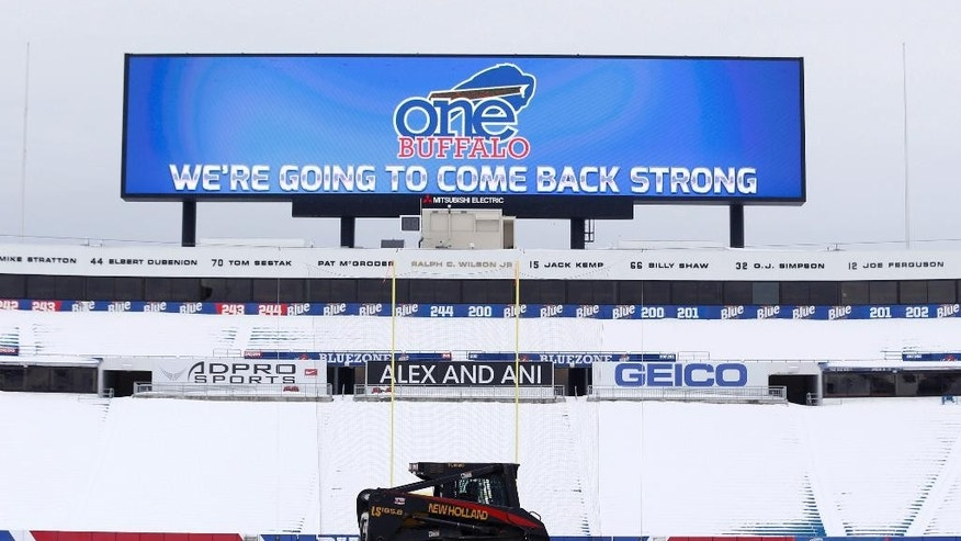 "Workers clear snow from the field at Ralph Wilson Stadium on Sunday, Nov. 23, 2014, in Orchard Park, N.Y. Snowed out today at the stadium, the Bills are in Detroit to play their ""home"" NFL football game against the New York Jets on Monday night, Nov. 24, 2014. (AP Photo/Mike Groll)"