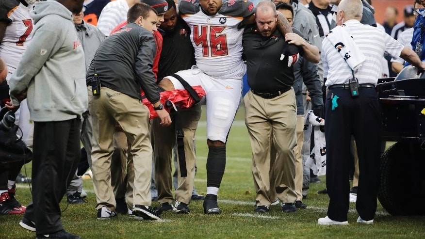 Tampa Bay Buccaneers fullback Jorvorskie Lane (46) is helped to a cart after an injury during the first half of an NFL football game against the Chicago Bears Sunday, Nov. 23, 2014, in Chicago. (AP Photo/Charles Rex Arbogast)