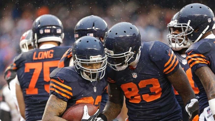 Chicago Bears running back Matt Forte (22) is congratulated by teammate Martellus Bennett (83) after his touchdown run during the second half of an NFL football game against the Tampa Bay Buccaneers Sunday, Nov. 23, 2014, in Chicago. (AP Photo/Nam Y. Huh)