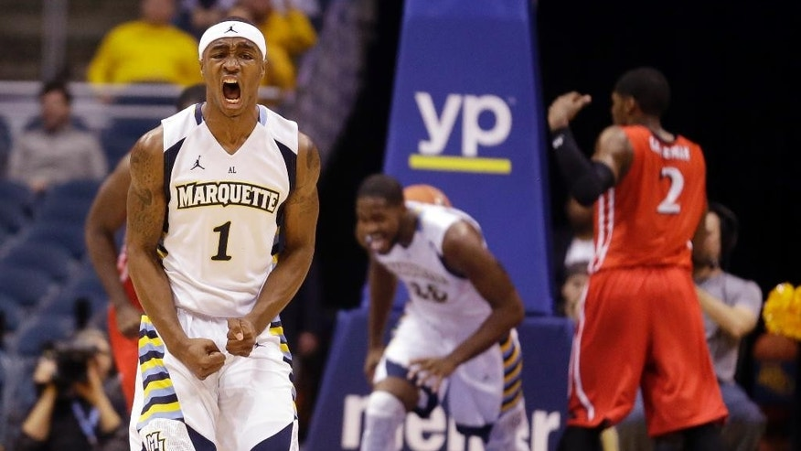 Marquette's Duane Wilson reacts after an assist to teammate Steve Taylor Jr. during the second half of an NCAA college basketball game against N.J.I.T. Monday, Nov. 24, 2014, in Milwaukee. (AP Photo/Morry Gash)