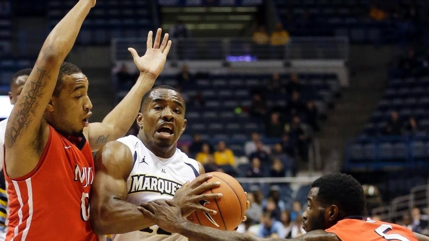 Marquette's Derrick Wilson tries to drive between N.J.I.T.'s Damon Lynn (5) and Ky Howard during the first half of an NCAA college basketball game Monday, Nov. 24, 2014, in Milwaukee. (AP Photo/Morry Gash)