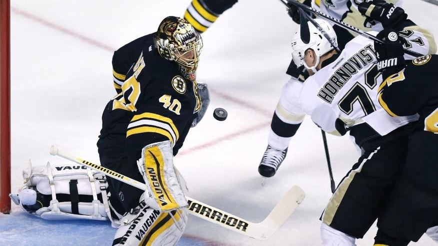 Boston Bruins goalie Tuukka Rask (40) makes a save as Pittsburgh Penguins right wing Patric Hornqvist (72) looks to play the rebound during the first period of an NHL hockey game in Boston, Monday, Nov. 24, 2014. (AP Photo/Charles Krupa)