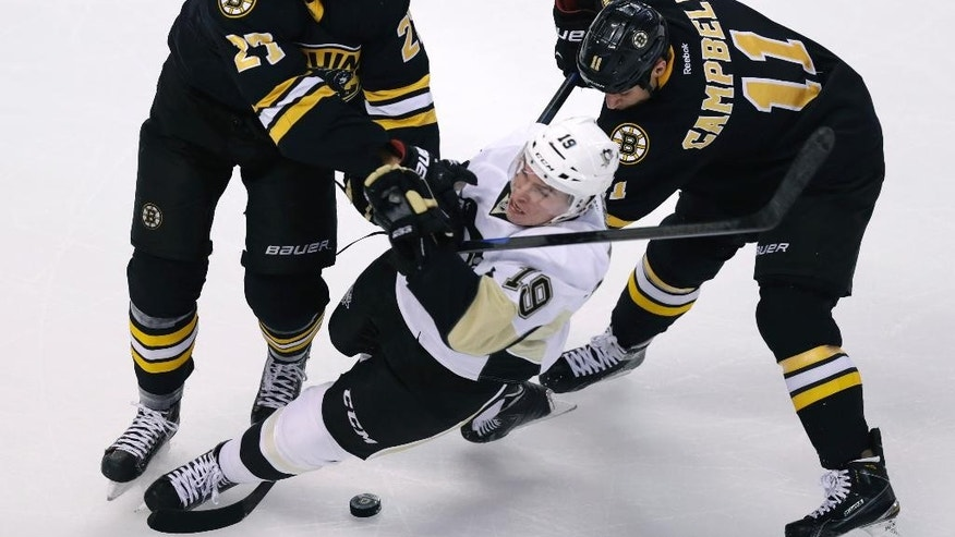 Pittsburgh Penguins right wing Beau Bennett (19) is dropped to the ice by Boston Bruins defenseman Dougie Hamilton (27) during the first period of an NHL hockey game in Boston, Monday, Nov. 24, 2014. At right trying to dig out the puck is Bruins center Gregory Campbell. (AP Photo/Charles Krupa)