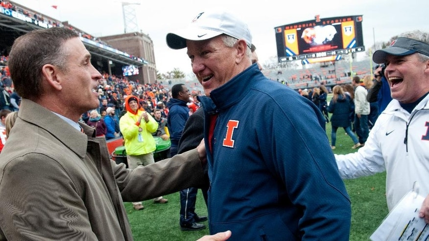Illinois athletic director Mike Thomas, left, greets offensive coordinator Bill Cubit and head coach Tim Beckman, right, after beating Penn State in an NCAA football game Saturday, Nov. 22, 2014, at Memorial Stadium in Champaign, Ill. (AP Photo/Bradley Leeb)