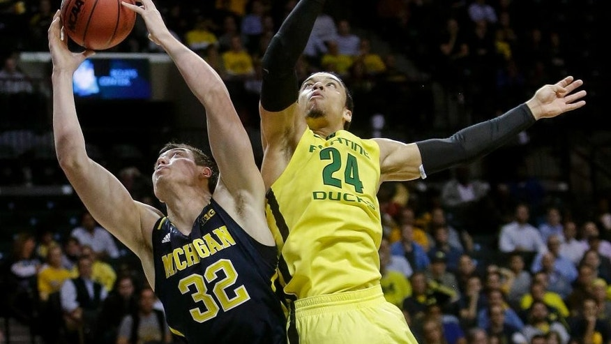 Michigan's Ricky Doyle (32) fights for control of the ball with Oregon's Dillon Brooks (24) during the first half of an NCAA college basketball game Monday, Nov. 24, 2014, in New York. (AP Photo/Frank Franklin II)