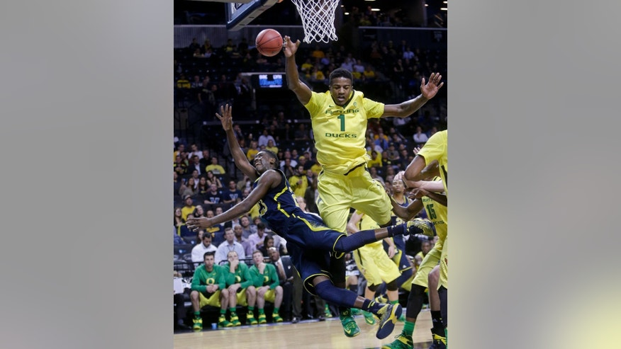 Oregon's Jordan Bell (1) fouls Michigan's Caris LeVert (23) during the first half of an NCAA college basketball game Monday, Nov. 24, 2014, in New York. (AP Photo/Frank Franklin II)