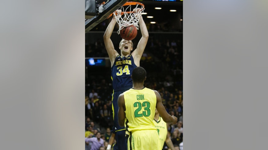 Michigan's Mark Donnal (34) dunks the ball in front of Oregon's Elgin Cook (23) during the first half of an NCAA college basketball game Monday, Nov. 24, 2014, in New York. (AP Photo/Frank Franklin II)