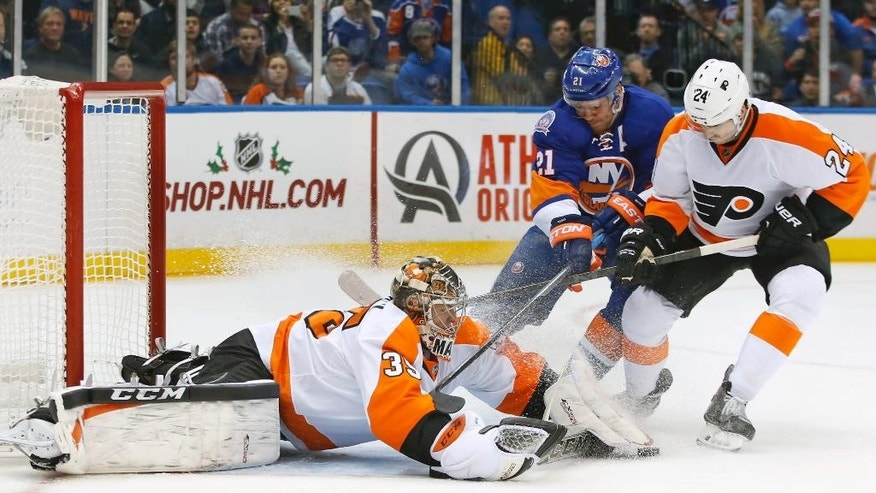 New York Islanders right wing Kyle Okposo (21) and Philadelphia Flyers right wing Matt Read (24) battle for control of the puck in front of Philadelphia Flyers goalie Steve Mason (35) in the second period of an NHL hockey game at Nassau Coliseum in Uniondale, N.Y., Monday, Nov. 24, 2014. (AP Photo/Kathy Willens)