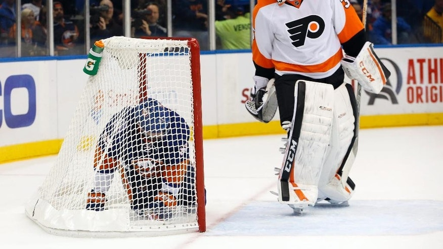 Philadelphia Flyers goalie Steve Mason (35) looks over his shoulder at New York Islanders defenseman Johnny Boychuk who was knocked into the net in the second period of an NHL hockey game at Nassau Coliseum in Uniondale, N.Y., Monday, Nov. 24, 2014. (AP Photo/Kathy Willens)