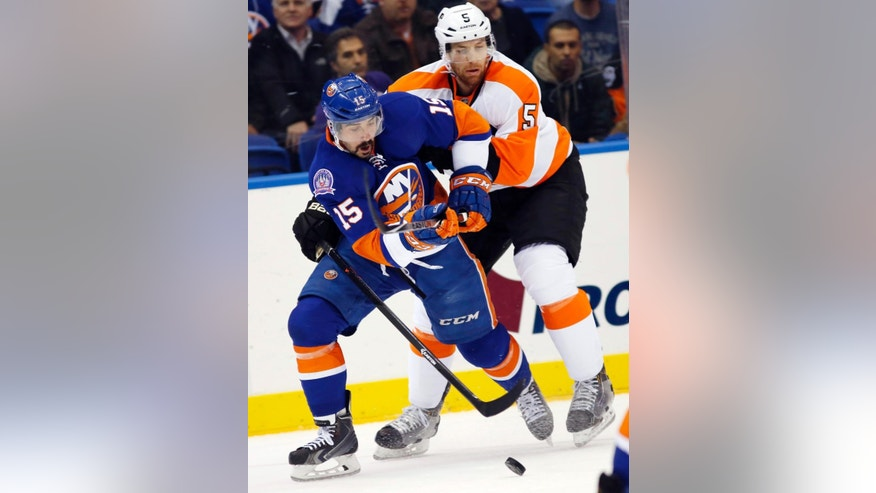 Philadelphia Flyers defenseman Braydon Coburn (5) defends New York Islanders right wing Cal Clutterbuck (15) in the first period of an NHL hockey game at Nassau Coliseum in Uniondale, N.Y., Monday, Nov. 24, 2014. (AP Photo/Kathy Willens)