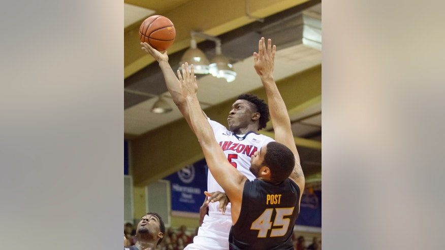 Arizona forward Stanley Johnson (5) slides past Missouri forward Keanau Post (45) to shoot a layup in the first half of an NCAA college basketball game at the Maui Invitational on Monday, Nov. 24, 2014, in Lahaina, Hawaii. (AP Photo/Eugene Tanner)