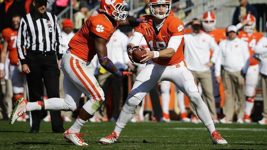 FILE - In this Nov. 15, 2014, file photo ,Clemson quarterback Cole Stoudt, right, hands off to teammate Wayne Gallman in the second half of an NCAA college football game against Georgia Tech in Atlanta. Clemson coach Dabo Swinney's got a message for Tiger fans who might boo senior quarterback Cole Stoudt on Saturday: Get a life. Swinney defended Stoudt, who'll start Saturday when Clemson takes on Georgia State.  (AP Photo/David Goldman, File)