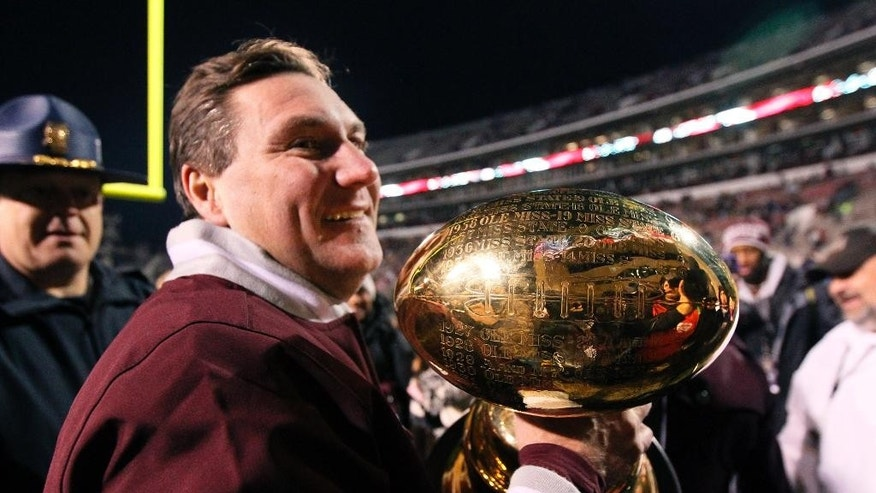 FILE - In this Nov. 28, 2013, file photo, Mississippi State coach Dan Mullen carries the Egg Bowl trophy after his team beat Mississippi 17-10 in overtime in an NCAA college football game in Starkville, Miss. No. 4 Mississippi State has been at its best during Egg Bowl week during Dan Mullen's coaching tenure, winning four out of five in the rivalry. (AP Photo/Rogelio V. Solis, File)
