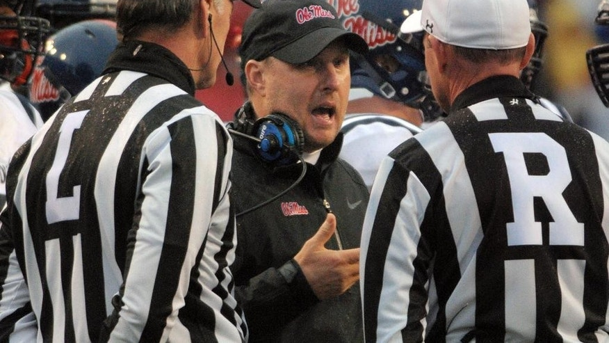 Mississippi coach Hugh Freeze talks to officials during a timeout in the first quarter of an NCAA college football game against Arkansas Saturday, Nov. 22, 2014, in Fayetteville, Ark. (AP Photo/David Quinn)