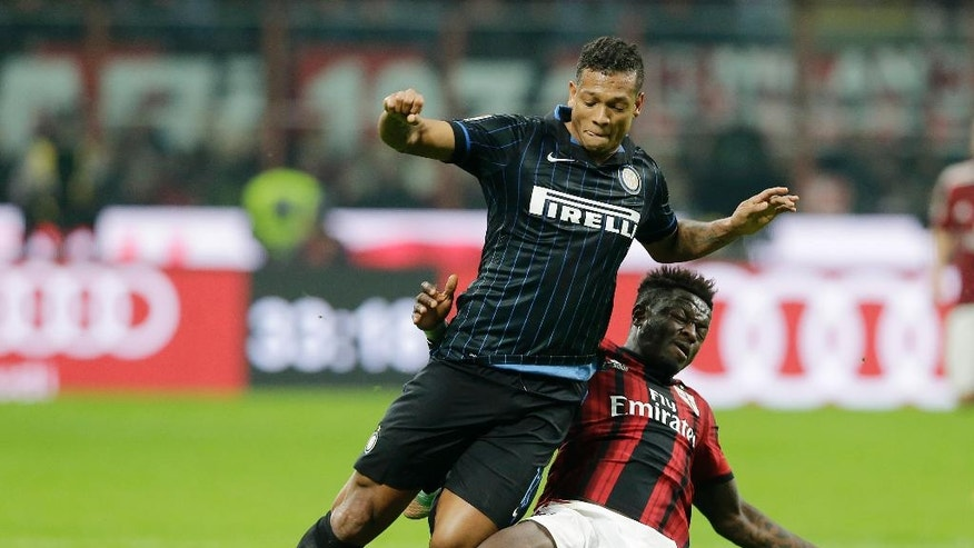 Inter Milan's Fredy Guarin, left, is tackled by AC Milan's Sulley Muntari during the Serie A soccer match between AC Milan and Inter Milan at the San Siro stadium in Milan, Italy, Sunday, Nov. 23, 2014. (AP Photo/Antonio Calanni)