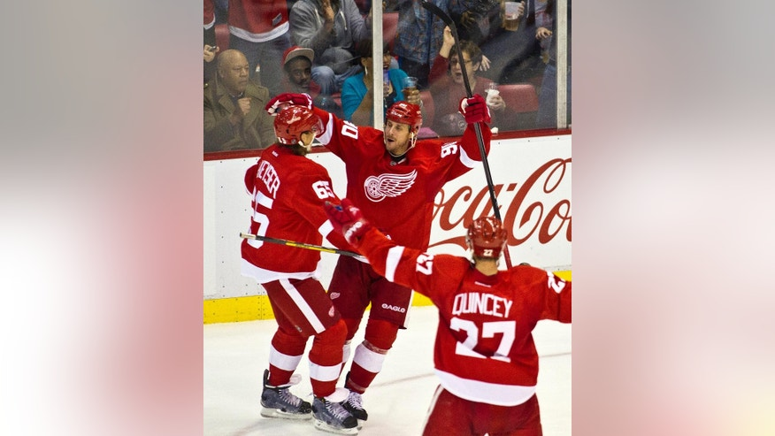 Detroit Red Wings forward Stephen Weiss, middle, celebrates his goal with defenseman Danny DeKeyser, left, and defenseman Kyle Quincey (27), during the second period of an NHL hockey game against the Ottawa Senators in Detroit, Monday, Nov. 24, 2014. (AP Photo/Tony Ding)