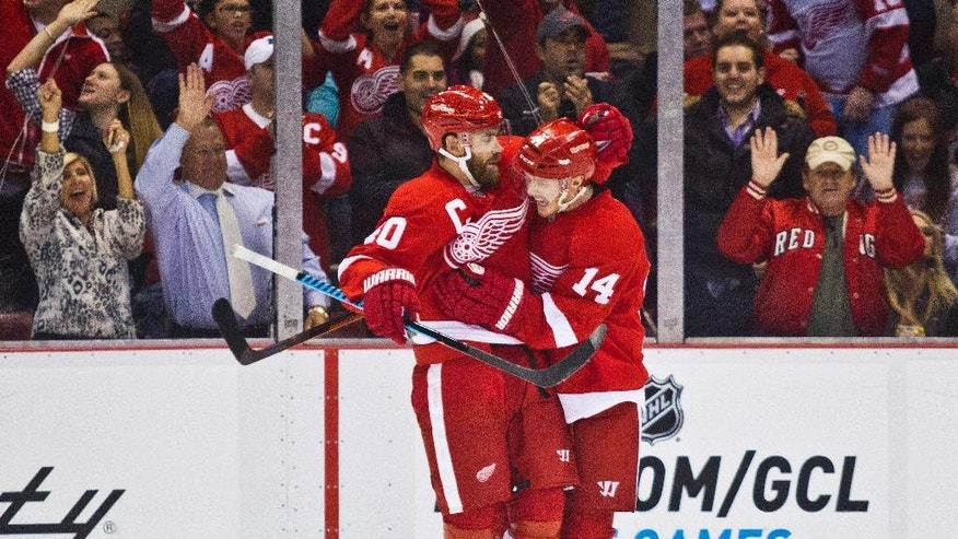 Detroit Red Wings forward Henrik Zetterberg (40), of Sweden, celebrates with forward Gustav Nyquist (14), of Sweden, after Nyquist scored a goal during the first period of an NHL hockey game against the Ottawa Senators in Detroit, Monday, Nov. 24, 2014. (AP Photo/Tony Ding)