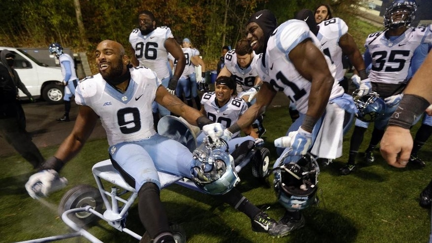 North Carolina's Travis Hughes (9) sprays paint and rides the victory bell with teammates following a 45-20 win over Duke in an NCAA college football game in Durham, N.C., Thursday, Nov. 20, 2014. (AP Photo/Gerry Broome)