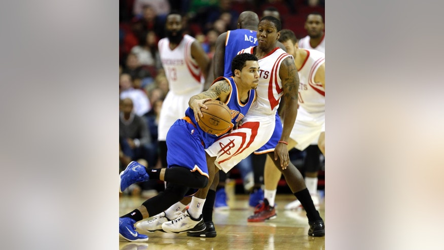 New York Knicks' Shane Larkin, left, is fouled by Houston Rockets' Isaiah Canaan, right, during the third quarter of an NBA basketball game Monday, Nov. 24, 2014, in Houston. (AP Photo/David J. Phillip)