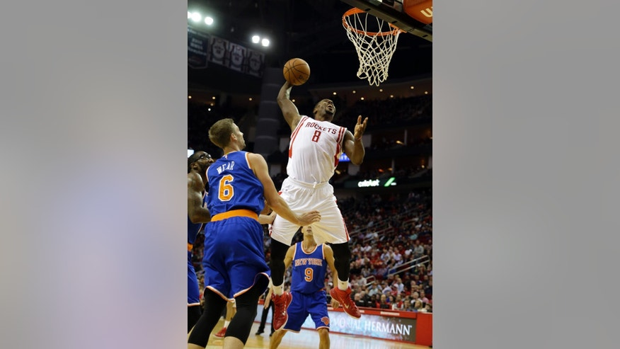 Houston Rockets' Joey Dorsey (8) is fouled by New York Knicks' Travis Wear (6) during the third quarter of an NBA basketball game Monday, Nov. 24, 2014, in Houston. (AP Photo/David J. Phillip)