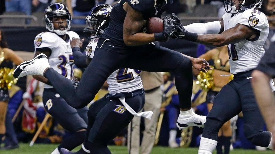 New Orleans Saints wide receiver Marques Colston (12) pulls in a touchdown reception in front of Baltimore Ravens strong safety Matt Elam (26) and free safety Terrence Brooks (31) in the first half of an NFL football game in New Orleans, Monday, Nov. 24, 2014. (AP Photo/Jonathan Bachman)