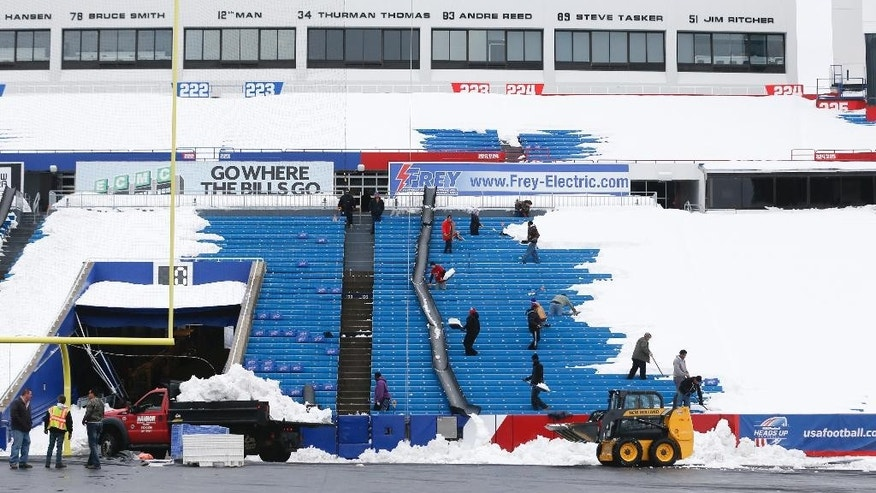 "Workers clear snow from Ralph Wilson Stadium on Sunday, Nov. 23, 2014, in Orchard Park, N.Y. Snowed out today at the stadium, the Bills are in Detroit to play their ""home"" NFL football game against the New York Jets on Monday night, Nov. 24, 2014. (AP Photo/Mike Groll)"