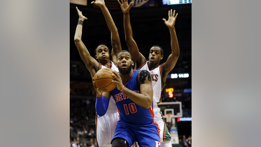 Detroit Pistons' Greg Monroe looks to shoot in front of Milwaukee Bucks' John Henson, left, and Khris Middleton, right, during the first half of an NBA basketball game Tuesday, Nov. 25, 2014, in Milwaukee. (AP Photo/Morry Gash)