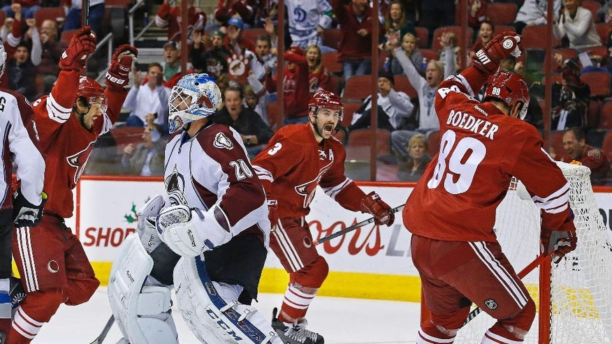 Arizona Coyotes center Antoine Vermette (50), defenseman Keith Yandle (3) and left wing Mikkel Boedker (89) celebrate following Vermette's goal against the Colorado Avalanche during the first period of an NHL hockey game Tuesday, Nov. 25, 2014, in Glendale, Ariz. (AP Photo/The Arizona Republic, David Kadlubowski)