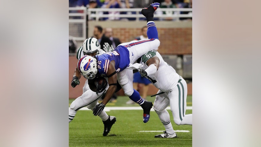 Buffalo Bills running back Anthony Dixon (26) is upended by New York Jets defensive end Sheldon Richardson (91) during the first half of an NFL football game in Detroit, Monday, Nov. 24, 2014. (AP Photo/Duane Burleson)