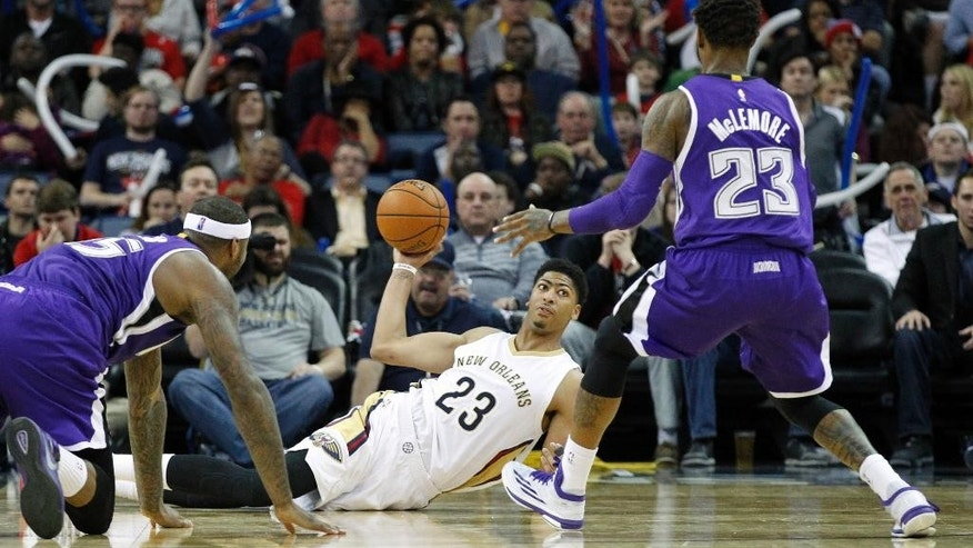 New Orleans Pelicans forward Anthony Davis (23) throws a pass while lying on the floor after recovering a loose ball from Sacramento Kings guard Ben McLemore (23) and center DeMarcus Cousins (15) in the second half of an NBA basketball game in New Orleans, Tuesday, Nov. 25, 2014.  (AP Photo/Butch Dill)