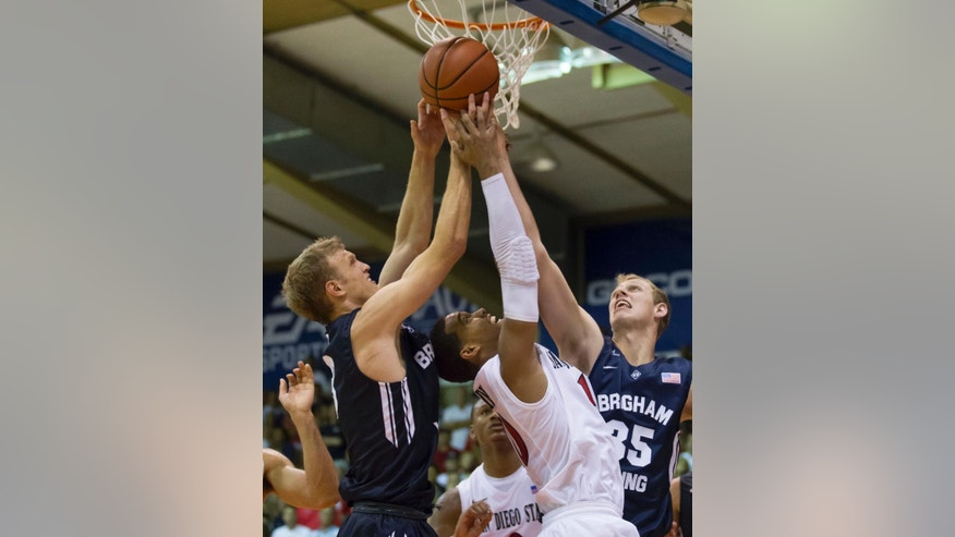 San Diego State guard Aqeel Quinn, center, battles Brigham Young guard Tyler Haws, left, and his teammate forward Isaac Neilson, right, for a rebound in the second half of an NCAA college basketball game at the Maui Invitational on Monday, Nov. 24, 2014, in Lahaina, Hawaii. San Diego State beat Brigham Young 92-87 in double overtime. (AP Photo/Eugene Tanner)