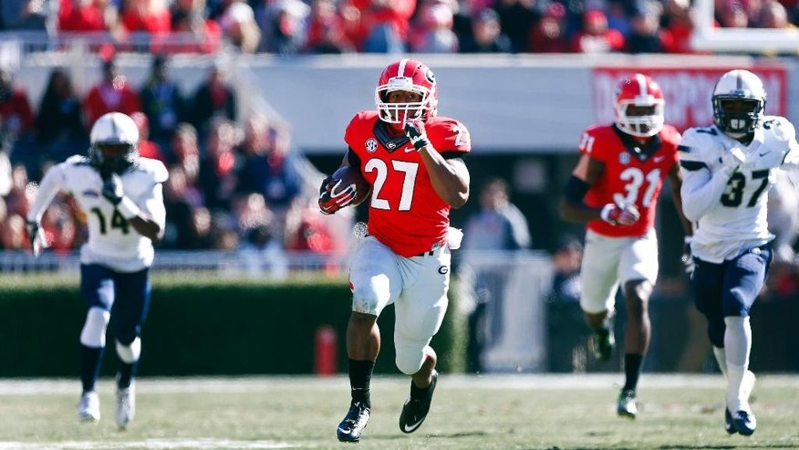 Georgia running back Nick Chubb (27) breaks free for a touchdown as Charleston Southern defensive backs Malcolm Jackson (14) and Davion Anderson (37) give chase during the first half of an NCAA college football game, Saturday, Nov. 22, 2014, in Athens, Ga. (AP Photo/John Bazemore)