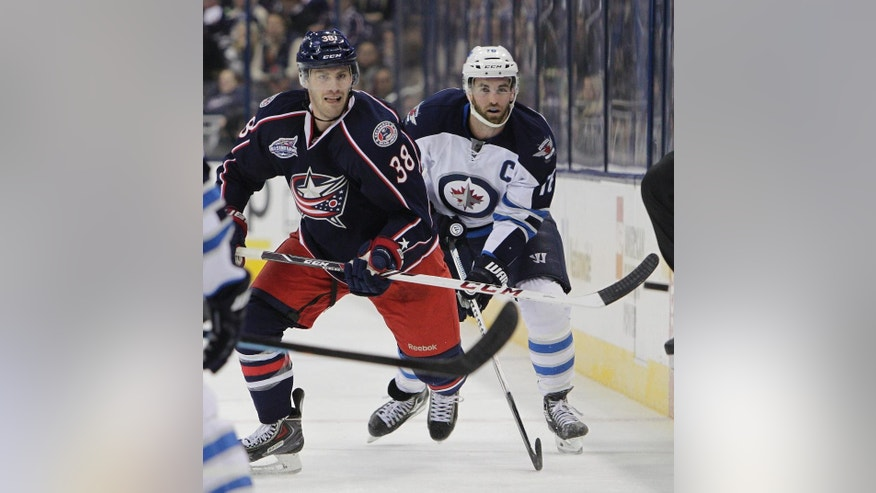 Columbus Blue Jackets' Boone Jenner, left, and Winnipeg Jets' Andrew Ladd chase a loose puck during the second period of an NHL hockey game Tuesday, Nov. 25, 2014, in Columbus, Ohio. (AP Photo/Jay LaPrete)