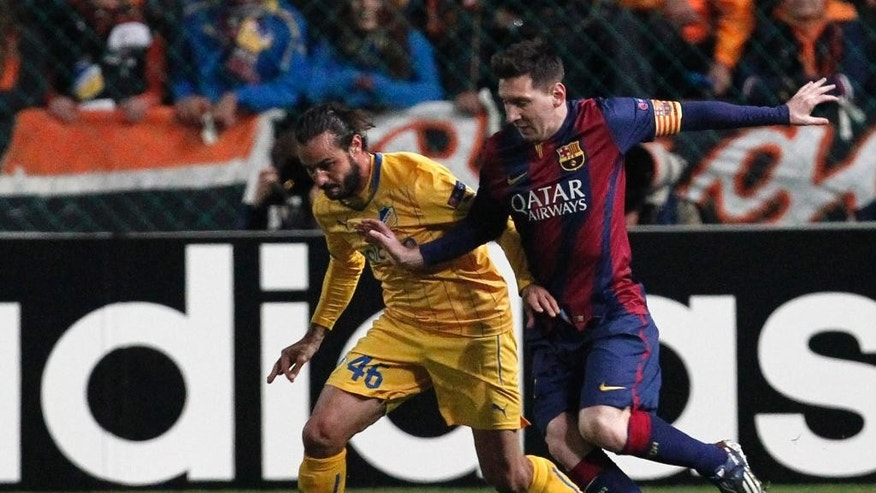 APOEL's Efstathios Aloneftis fights for the ball with Barcelona's Lionel Messi during a Champions League Group F soccer match between APOEL and FC Barcelona at GSP stadium, in Nicosia, Cyprus, Tuesday, Nov. 25, 2014. (AP Photo/Petros Karadjias)