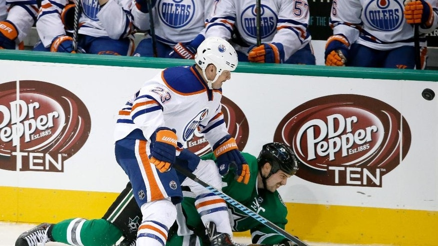 Dallas Stars' Jamie Benn (14) falls to the ice after a collision with Edmonton Oilers' Matt Hendricks (23) as the two chased a loose puck in the third period of an NHL hockey game, Tuesday, Nov. 25, 2014, in Dallas. The Stars won 3-2. (AP Photo/Tony Gutierrez)