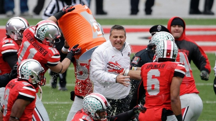 FILE - In this Nov. 24, 2012, file photo, Ohio State head coach Urban Meyer, center, gets doused by senior wide receiver Jake Stoneburner (11) after a win over Michigan in an NCAA college football game in Columbus, Ohio. Every year except one from 1935-2012, the Ohio State Buckeyes were able to focus entirely on their annual season-ending rivalry with Michigan. But now, for the second year in a row, not only do they have the Wolverines to deal with but also the Big Ten title game looming a week later. (AP Photo/Mark Duncan, File)
