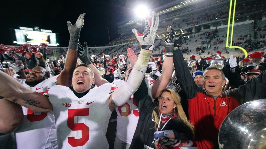 FILE - In this Nov. 9, 2014, file photo, Ohio State's Jeff Heuerman (5), coach Urban Meyer, right, and Meyer's wife, Shelley, celebrate following the team's 49-37 win over Michigan State in an NCAA college football game in East Lansing, Mich. Every year except one from 1935-2012, the Ohio State Buckeyes were able to focus entirely on their annual season-ending rivalry with Michigan. But now, for the second year in a row, not only do they have the Wolverines to deal with but also the Big Ten title game looming a week later. (AP Photo/Al Goldis, File)