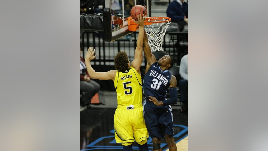 Villanova's Dylan Ennis (31) blocks a shot by Michigan's D.J. Wilson (5) during the first half of an NCAA college basketball game Tuesday, Nov. 25, 2014, in New York. (AP Photo/Frank Franklin II)