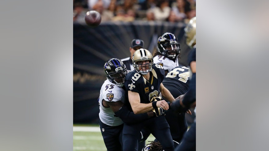 New Orleans Saints quarterback Drew Brees (9) watches his pass, which was intercepted for a touchdown, as he is hit by Baltimore Ravens outside linebacker Terrell Suggs (55) in the second half of an NFL football game in New Orleans, Monday, Nov. 24, 2014. (AP Photo/Rogelio Solis)
