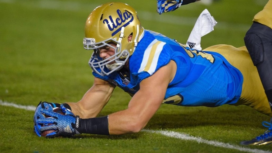 UCLA fullback Taylor Lagace recovers a punt that was fumbled by Southern California's Nelson Agholor during the first half of an NCAA college football game, Saturday, Nov. 22, 2014, in Pasadena, Calif. (AP Photo/Mark J. Terrill)