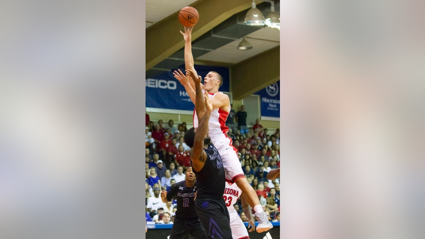 Arizona center Kaleb Tarczewski, top, takes a jump shot over Kansas State forward Thomas Gipson, bottom in the first half of an NCAA college basketball game at the Maui Invitational on Tuesday, Nov. 25, 2014, in Lahaina, Hawaii. Kansas State guard Marcus Foster (2) looks on during the play. (AP Photo/Eugene Tanner)