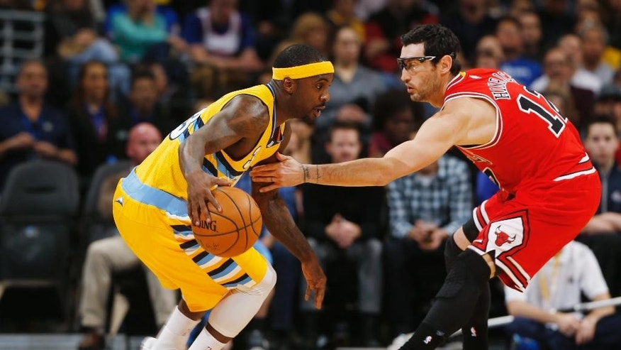 Denver Nuggets guard Ty Lawson, left, tries to work ball inside for shot as Chicago Bulls guard Kirk Hinrich covers in the first quarter of an NBA basketball game in Denver on Tuesday, Nov. 25, 2014. (AP Photo/David Zalubowski)