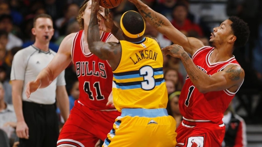 Chicago Bulls guard Derrick Rose, right, reaches up to knock ball away from Denver Nuggets guard Ty Lawson, center, as Bulls forward Cameron Bairstow, left, of Australia, covers in the first quarter of an NBA basketball game in Denver on Tuesday, Nov. 25, 2014. (AP Photo/David Zalubowski)