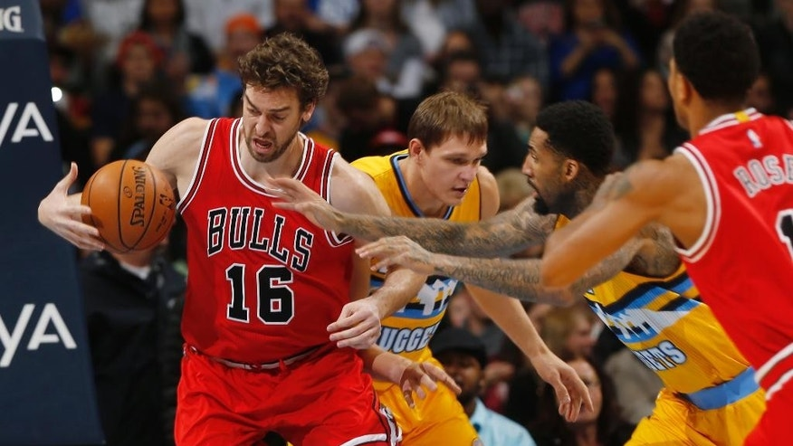From left, Chicago Bulls center Pau Gasol, of Spain, pulls in loose ball in front of Denver Nuggets center Timofey Mozgov, of Russia, and forward Wilson Chandler as Bulls guard Derrick Rose comes in to help Gasol in the first quarter of an NBA basketball game in Denver on Tuesday, Nov. 25, 2014. (AP Photo/David Zalubowski)