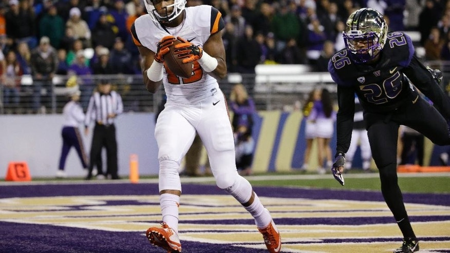 Oregon State's Jordan Villamin, left, scores in front of Washington's Sidney Jones during the first of an NCAA college football game Saturday, Nov. 22, 2014, in Seattle. (AP Photo/Elaine Thompson)