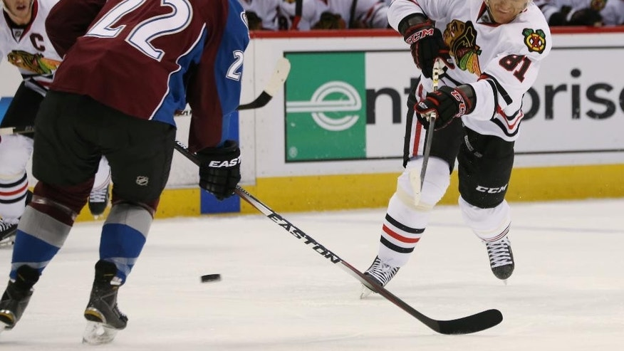 Chicago Blackhawks right wing Marian Hossa, right, of Slovakia, takes shot as Colorado Avalanche defenseman Zach Redmond covers in the second period of an NHL hockey game in Denver on Wednesday, Nov. 26, 2014. (AP Photo/David Zalubowski)